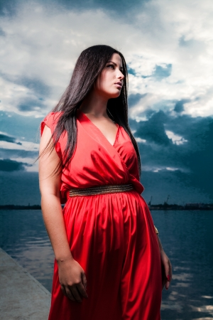 Adorable brunette with red dress posing on a dawn looking away  Fashion Beauty  Outdoors shot  photo