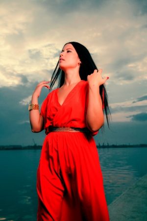 Adorable brunette with red dress posing on a dawn looking up  Fashion Beauty  Outdoors shot  photo