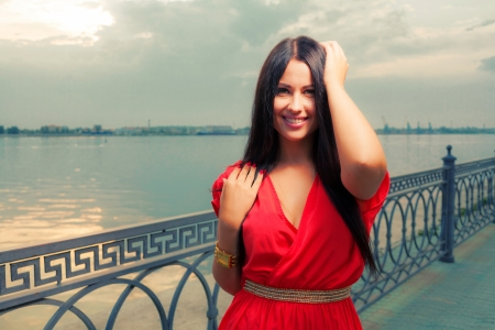 Adorable brunette with red dress posing on a dawn on riverside near water   Fashion Beauty  Outdoors shot  photo