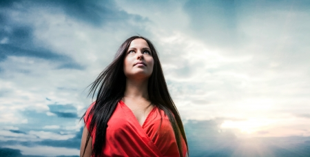 Hope concept  Pretty brunette with red dress posing on a dawn against evening sky   Fashion Beauty  Outdoors shot  photo