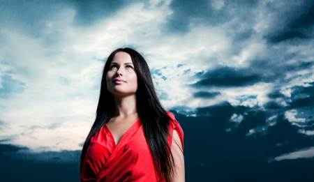 Brunette girl in red dress against dramatic sky  Outdoor fashion shot photo