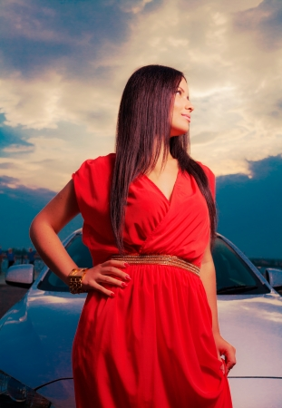 Adorable brunette with red dress posing against a dawn  Fashion Outdoors shot dramatic sky  photo