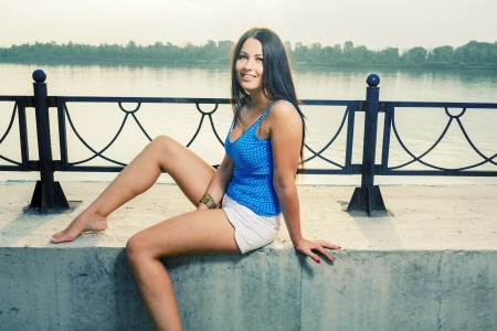 Beautiful young woman enjoy the breeze outdoor in a summer day sitting  near riverside photo