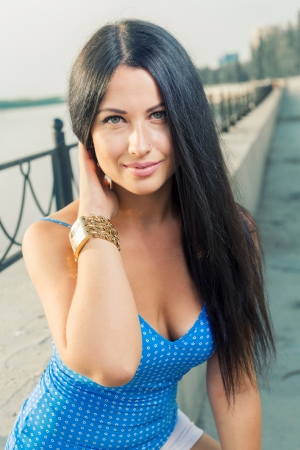 Beautiful young woman enjoy the breeze outdoor in a summer day in blue tank top photo