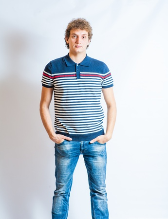 Young blonde adult caucasian man in casual clothes on a gray background. Not Isolated photo