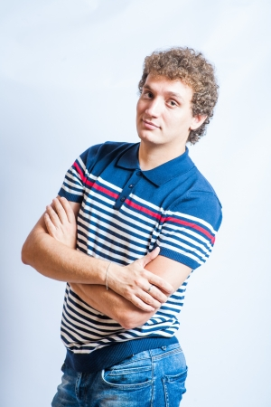 Portrait of handsome man with curly hairstyle smiling in studio background photo