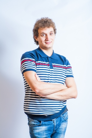 Student in casual wear. Man in stripped polo shirt on the gray background. Studio shot. photo