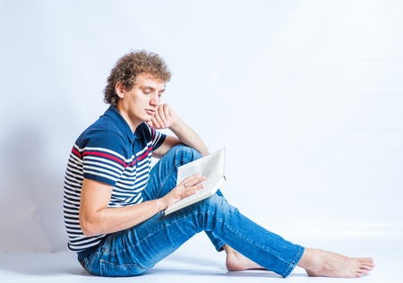 Handsome young student reading a book. Sitting on the gray background. Curly hair. Stock Photo - 21542536