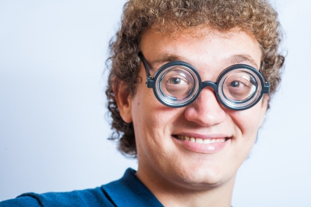 Closeup fun headshot of curly hair man smiling. Portrait of a man with nerd glasses n studio funny photo