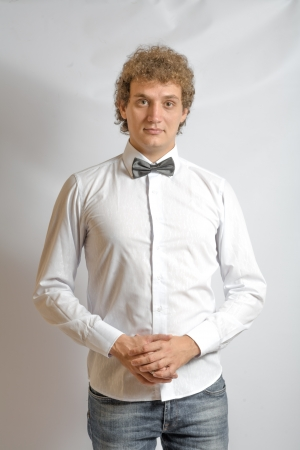 Fashionable boy blank expression. Curly hair, white shirt. Bow tie for something funny photo