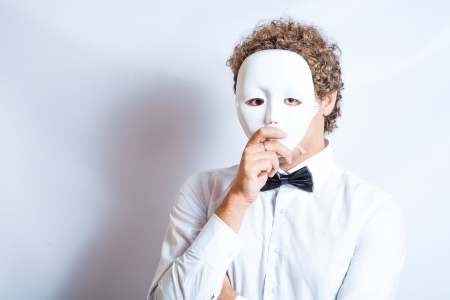 Face mime close-up emotion in thought, a black bow tie, theatrical white mask photo