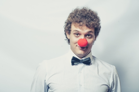 Young studen or Businessman with a red clown nose. Studio shot. Head and shoulders. Toned image Stock Photo