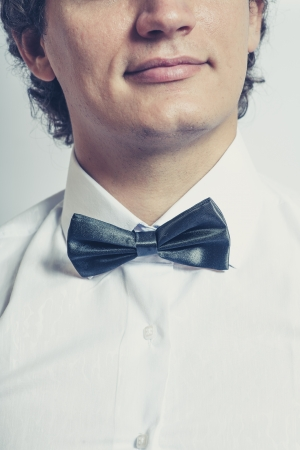 Toned image of the Stylish man in elegant black tuxedo, bow tie closeup and half of the face. Elegance concept. Stock Photo - 21562472