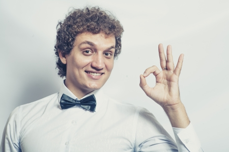 headshots: Funny businessman showing OK sign on studio shot. Toned image.