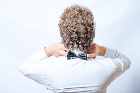 strangeness: Bow tie on the back side. Strangeness or fun concept. Back view of an elegant young fashion man in tuxedo on gray background, toned image. Touch bow tie by hands. Stock Photo
