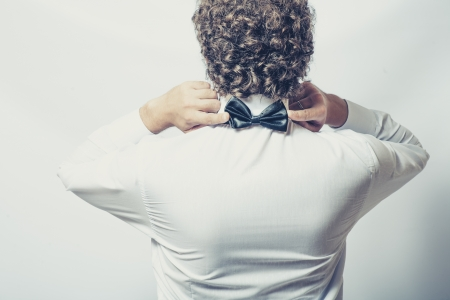 Bow tie on the back side. Strange or fun concept. Back view of an elegant young fashion man in tuxedo on gray background, toned image photo