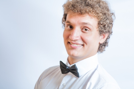 Closeup portrait of young business man in bow tie smiling photo