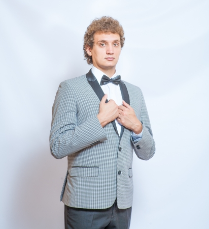 Square shot smiling curly man in black suit and bow tie photo