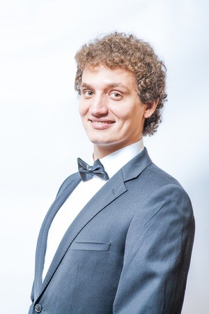 smiling curly man in black and bow tie photo