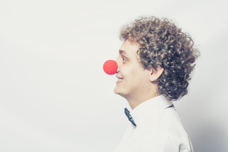 Profil de jeune �tudiant ou d'affaires avec un nez de clown rouge photo