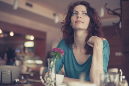 Waiting in loneliness - Young woman sitting in cafe on chair and looking away of camera photo