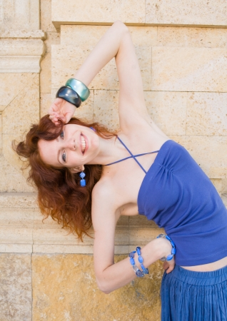 young redhead women outdoor in the street having fun, posing bended and smiling photo