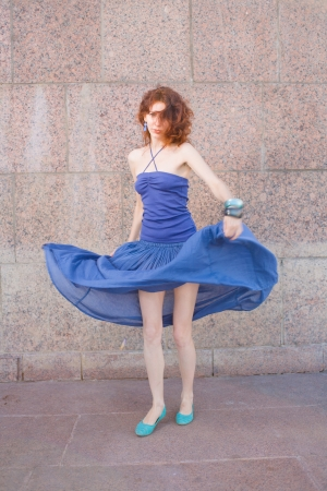 redhead 20s women in blue tank top and skirt dancing salsa outdoor in loneliness, summertime, day photo