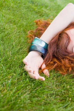 very  pretty red headed women laying on the fresh green grass and enjoy summertime photo