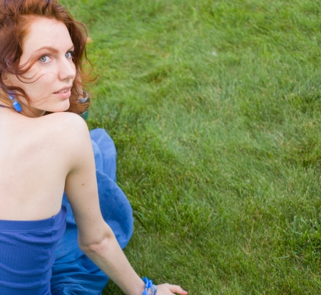 redhead women sitting on the green grass in summertime smiling photo