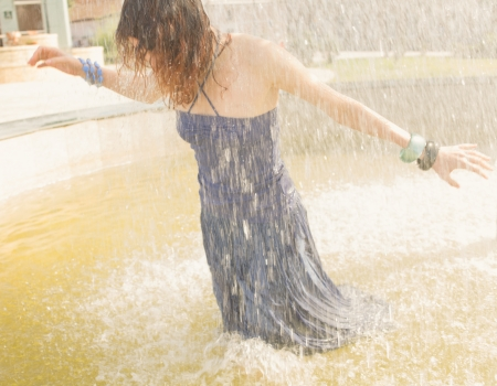 redhead women in the fountain in summertime under falling water, wet all is wet. Shot full of sunshine, Sunlit. Summer fun and enjoyment