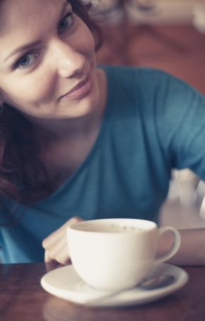 Redhead women sitting in the cafee with cup of coffee on the table befor and looking at camera photo