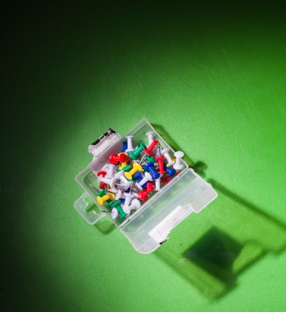 yellow tacks: image of mixed colors office push-pins in the plastic pack, angle view, on the green background, natural vignette made by flash light