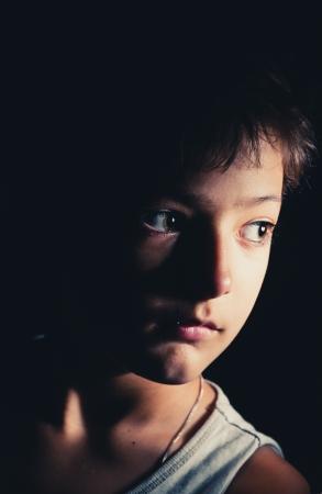 sad boy in the dark, focused light on the one side, toned image 免版税图像