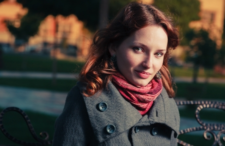 Red haired young female head and shoulders shot outside in autumn park, weared bright red scarf and coat  She looking at camera and smiling  Toned image
