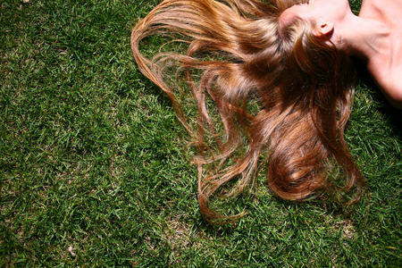 Young woman  no face  with long blond hair lying on the grass sleeping or thinking  photo