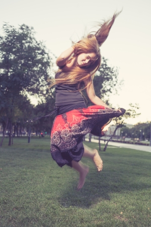 Girl jumping like flying bird. Hair by the wind. photo