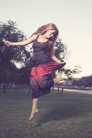 Long Haired Blonde  jumps on a green grass in evening time in city park . Girl jumping like flying bird. photo