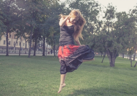 The young female jumps on a green grass in evening time in city park . Girl jumping like flying bird. photo
