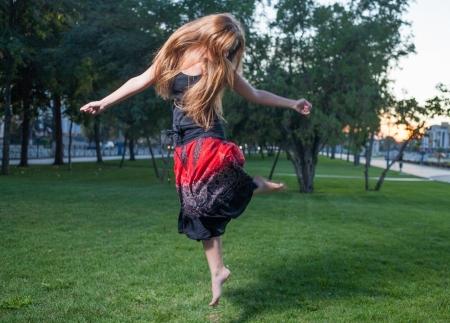 Long haired free style dancer. Girl jumping like flying bird. photo