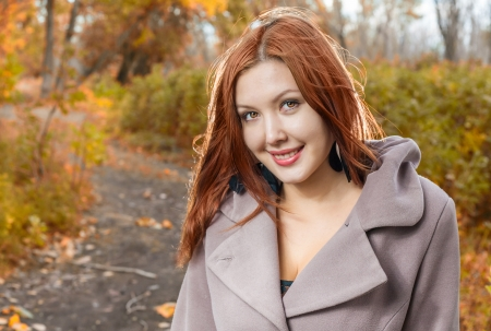 ginger haired: foxy-red haired women outdoors weared jacket at autumn time  Smiling and enjoy autumn air
