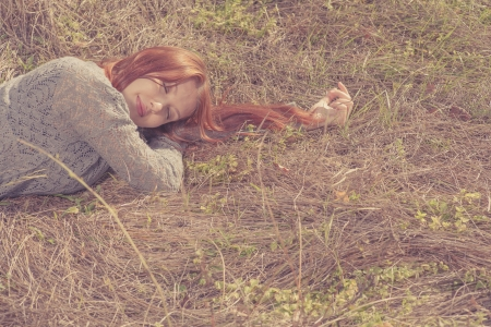red haired women lying on autumn grass photo