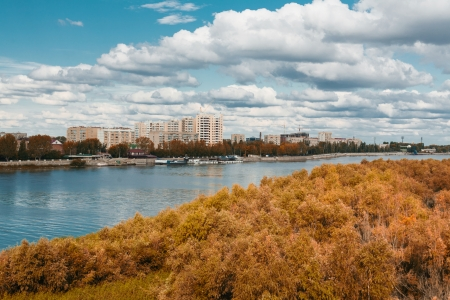 green forest, river, big sky and cityscape on the back Stock Photo