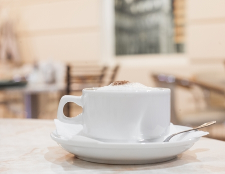 cappuchino: horizontal shot, cup of fresh cappuchino on the table, interior of cafe on background Stock Photo