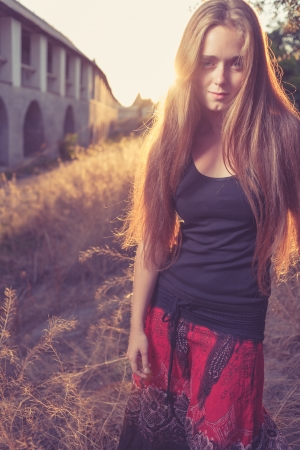 young blond women looking very seriously weared red skirt and black tank top   Against gold sunset light  Autumn time  Backlit photo
