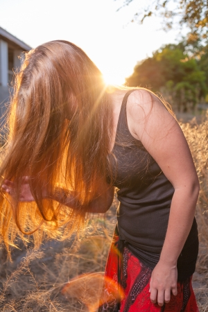 Young Pretty Woman In The Autumn Park at Sunset  Backlit  Her face hidden by long blond hair  Bended pose  Cute romantic girl, attractive blond woman enjoying autumn yellow sunlight  photo