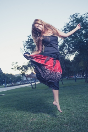 Dancing in park  Alone and happy  Long haired women make jump outdoors at evening  Vertical shot  Toned image photo
