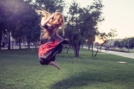 Blond haired women make jump outdoors at evening  Horizontal image  photo