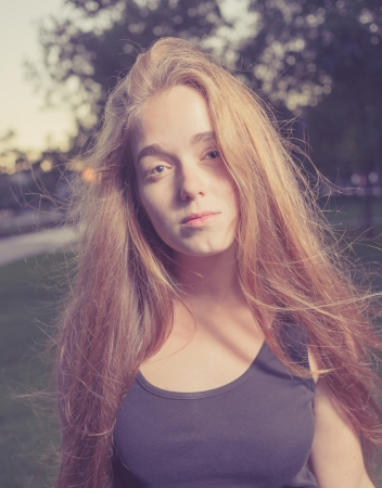 Portrait of a beautiful young woman in the city park  Outddors shot in the evening time  Toned Image Romantic girl, attractive 20s blond female enjoying autumn yellow sunlight