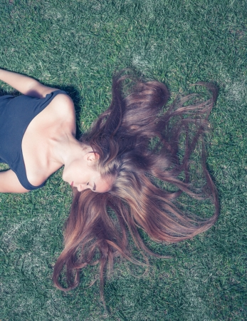 Crossprocess color image of the beautiful young girl is lying on green grass in the evening time  She enjoy summertime photo