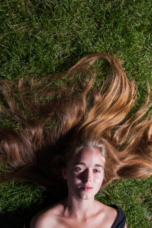 Head and shoulders shot of the beautiful young girl is lying on green grass in the evening time  Looking at camera  Blank expression on the face photo